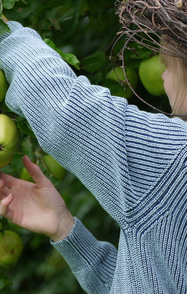 Close up. Raised ribbing knit pullover in light indigo blue. Piece of Blue